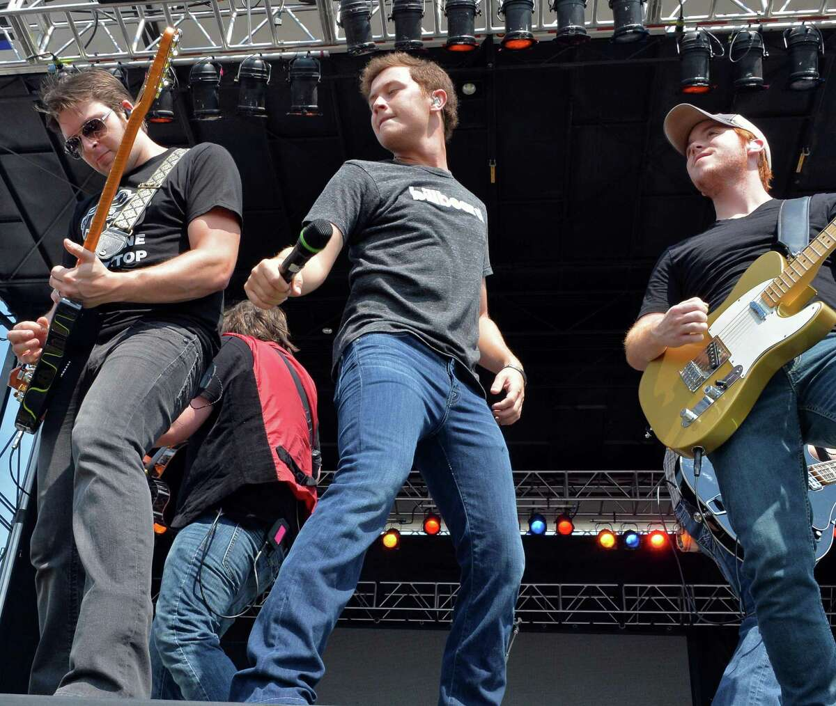 Scotty McCreery, center, performs with his band at the annual Countryfest show at the Schaghticoke Fairgrounds Saturday July 12, 2014, in Schagticoke, NY. (John Carl D'Annibale / Times Union)