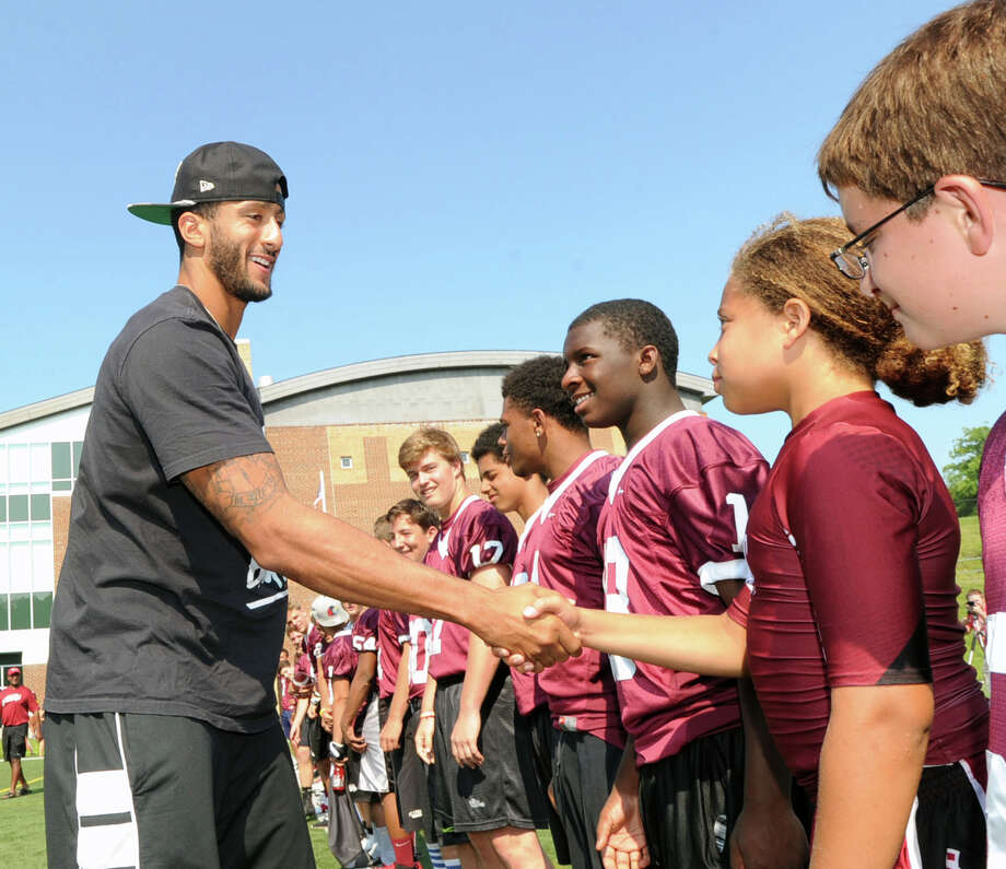 San Francisco 49ers quarterback Colin Kaepernick, left,  meets St. Luke's School football players during his visit to the St. Luke's School in New Canaan, Conn., Saturday afternoon, July 12, 2014. Kaepernick visited the school on behalf of the Children of Fallen Patriots Foundation that provides college scholarships and educational counseling to military children who have lost a parent in the line of duty. The foundation was founded by husband and wife, David and Cynthia Kim of Greenwich. Photo: Bob Luckey / Greenwich Time
