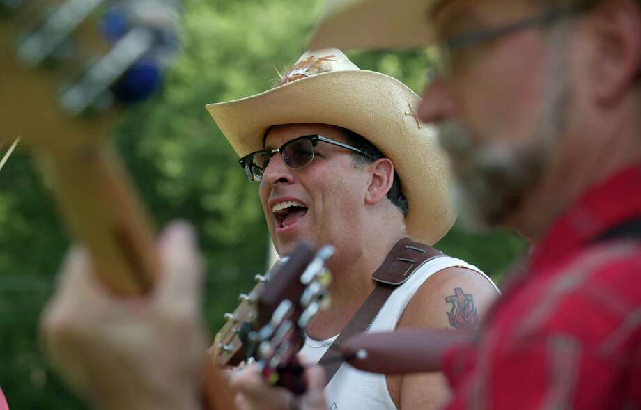 "Paul Fenick, 53, of Brookfield, warms up with the ""Still; River Ramblers"", of Brookfield, before they compete in the Roxbury Volunteer Fire Department annual  ""Pickin 'n' Fiddlin"" contest, on Saturday, July 12, 2014, held in Hurlburt Park, in Roxbury, Conn. This year is the 40th anniversary of the contest, which started in 1974. The categories of competition included, old time fiddle, mandolin, bluegrass banjo, fine pick guitar and others. Photo: H John Voorhees III / The News-Times Freelance"