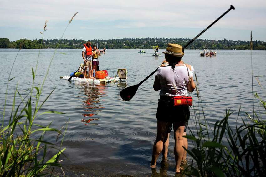 Spectators lined the shores of Green Lake to watch do-it-yourself-styled boats compete for prizes and bragging rights at the 43rd annual Seafair Milk Carton Derby Saturday, July 12, 2014, in Seattle, Wash. Nearly 100 colorful milk carton boats took part in the festivities.
