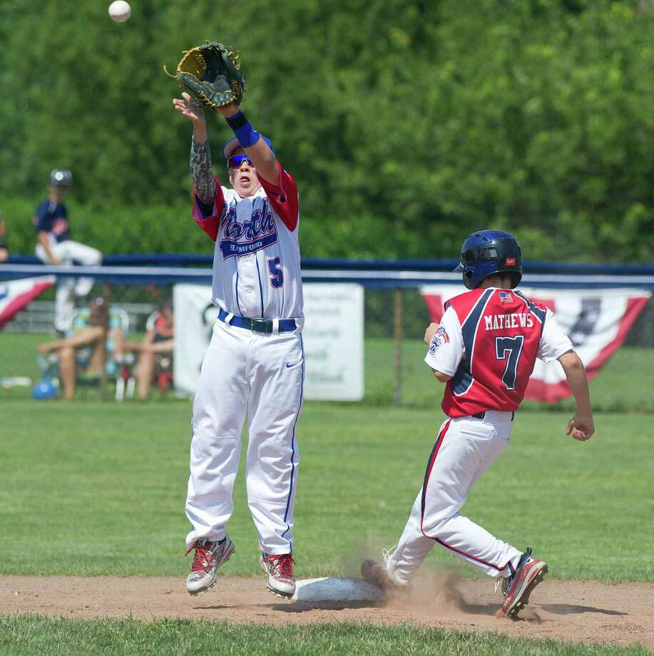 Norwalk's Jack Mathews safely steals second base as North Stamford's TJ Wainwright jumps up for the ball during Saturday's District 1 Little League Championship game at Frank Noto Field at West Beach in Stamford, Conn., on July 12, 2014. Photo: Lindsay Perry / Stamford Advocate