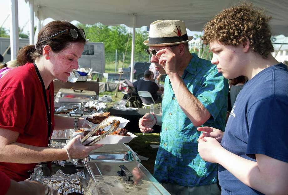 Michelle Lappas, left, serves ribs to Doug Friedenberg and his son, Kyrian, for judging during Saturday's Pork in the Park barbecue festival at Mill River Park in Stamford, Conn., on July 12, 2014. Photo: Lindsay Perry / Stamford Advocate