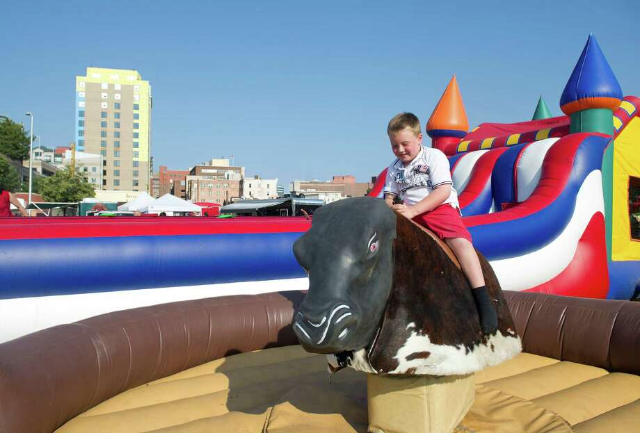 Jack Donovan, 6, rides a mechanical bull during Saturday's Pork in the Park barbecue festival at Mill River Park in Stamford, Conn., on July 12, 2014. Photo: Lindsay Perry / Stamford Advocate