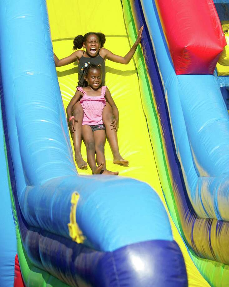 Miracle McBride, 11, and his sister, Blessin, 5, slide down an inflatable during Saturday's Pork in the Park barbecue festival at Mill River Park in Stamford, Conn., on July 12, 2014. Photo: Lindsay Perry / Stamford Advocate