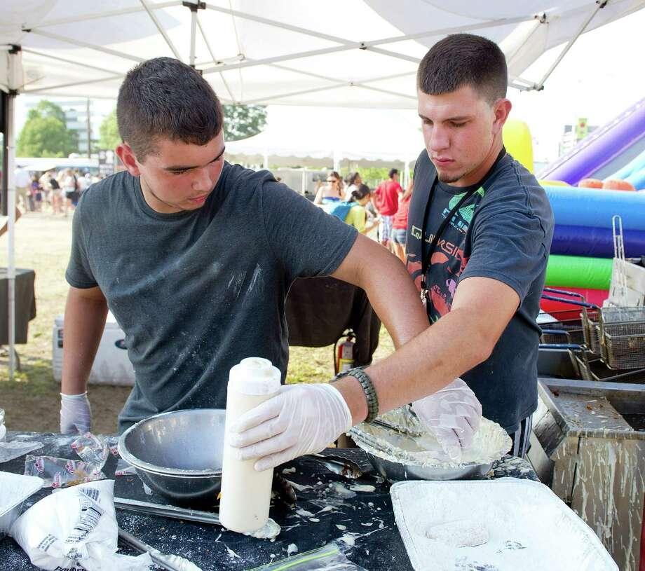 Chris Zeravica, left, and Kenny Otte, right, fry Twinkies, funnel cake, Oreos and other treats during Saturday's Pork in the Park barbecue festival at Mill River Park in Stamford, Conn., on July 12, 2014. Photo: Lindsay Perry / Stamford Advocate