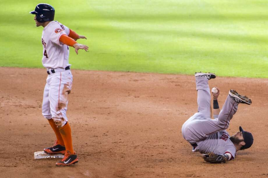 Boston second baseman Dustin Pedroia shows the ball after being pulled off the bag, leaving  George Springer safe at second on a single by Chris Carter and allowing Jose Altuve to score from third for the go-ahead run during the eighth inning. Photo: Smiley N. Pool, Houston Chronicle
