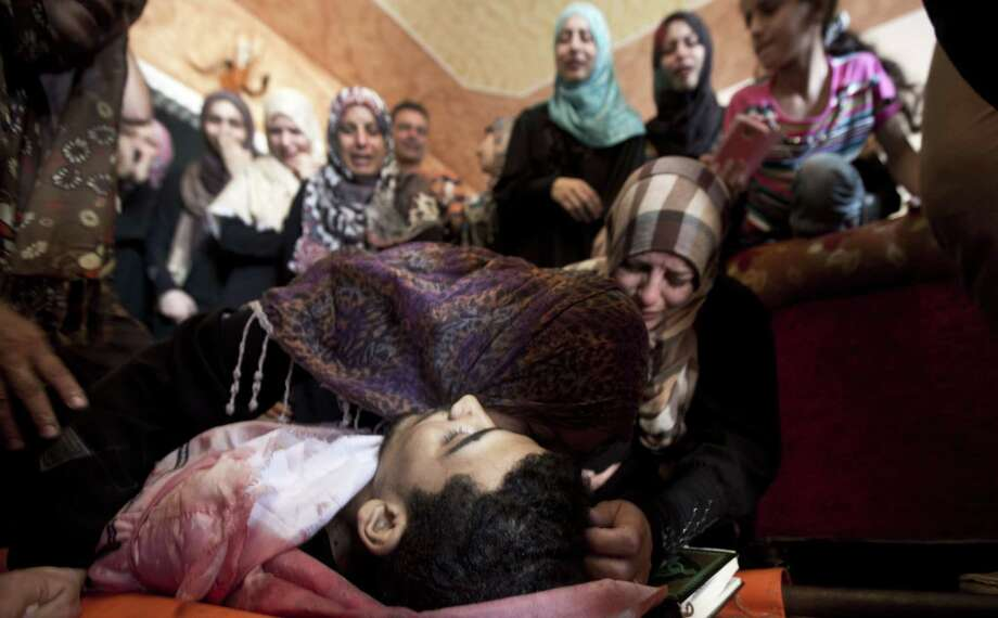 The mother and sister of Palestinian Mahmud al-Sewati mourn over his body during his funeral in Gaza City on July 12, 2014. Israel vowed no let-up in its aerial bombardment of Gaza, which has claimed more than 100 Palestinian lives, as a defiant Hamas rained more rockets on the Jewish state.  AFP PHOTO/MAHMUD HAMSMAHMUD HAMS/AFP/Getty Images Photo: MAHMUD HAMS / AFP