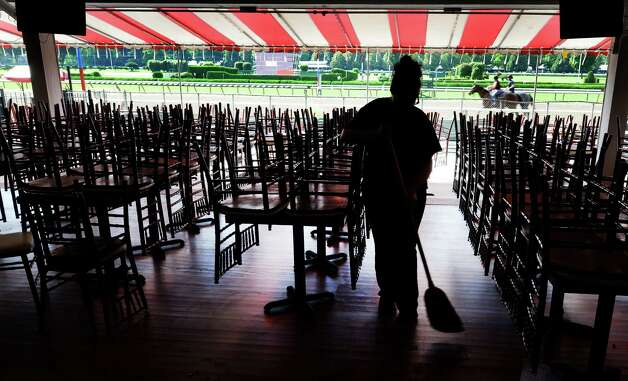 Cassaundra Ocasio of American Maintenance puts a broom to the floor of the Clubhouse as horses exercise in the background at the Saratoga Race Course Wednesday morning July 9, 2014 in preparation for Sunday's Family Day at the historic thoroughbred track in Saratoga Springs, N.Y.           (Skip Dickstein / Times Union) Photo: SKIP DICKSTEIN
