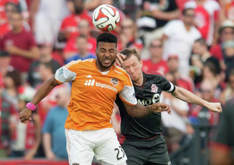 Houston Dynamo's Giles Barnes, left, and Toronto FC's Steven Caldwell battle for the ball during the first half of MLS soccer action in Toronto on Saturday, July 12, 2014. (AP Photo/The Canadian Press, Darren Calabrese) Photo: Darren Calabrese, Associated Press / CP