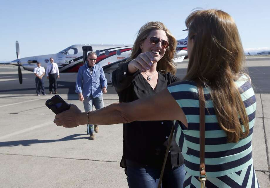 Amelia Rose Earhart, center, with co-pilot Shane Jordan, left, of Colorado, is greeted by her mom, Debborah Dale, right, as they arrive at North Field in Oakland, Calif., on Friday, July 11, 2014. Photo: Jane Tyska, AP/Oakland Tribune-Bay Area News Group