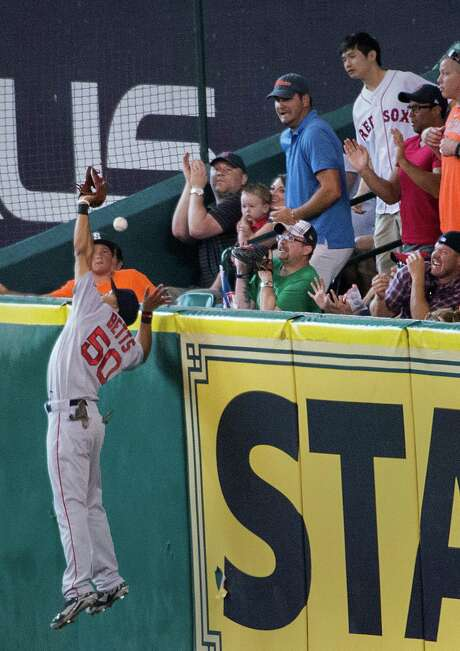 Red Sox right fielder Mookie Betts (50) makes a bid to deny the Astros' Jason Castro a home run in the third inning. But Betts comes up empty-handed, much to the fans' delight Saturday at Minute Maid Park. Photo: Smiley N. Pool / © 2014  Smiley N. Pool