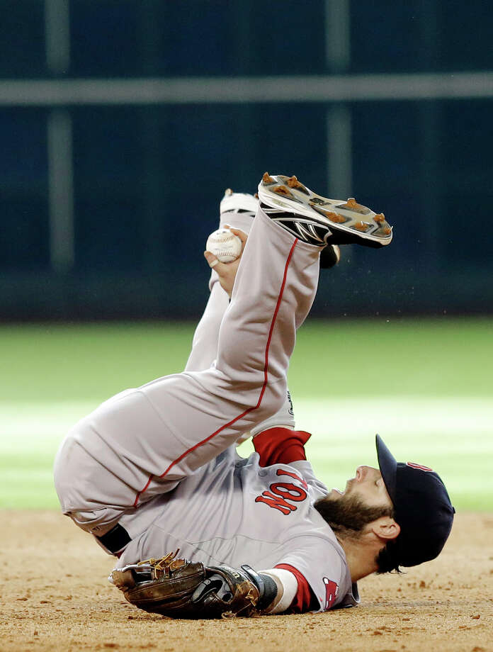 Boston Red Sox second baseman Dustin Pedroia holds up the ball while lying on his back after a double by Houston Astros' Jose Altuve in the eighth inning of a baseball game Saturday, July 12, 2014, in Houston. (AP Photo/Pat Sullivan) ORG XMIT: HTA114 Photo: Pat Sullivan / AP