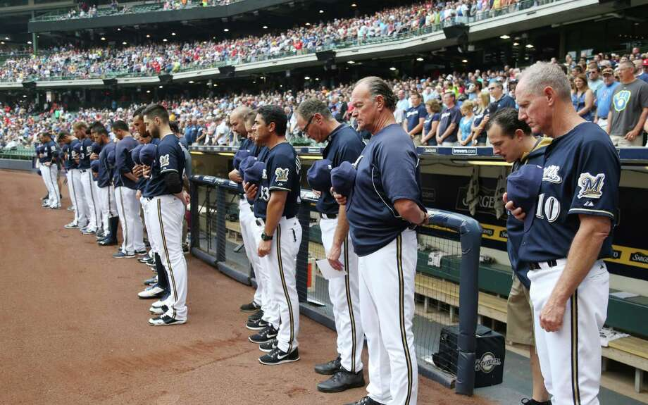 Milwaukee Brewers Manager Ron Roenicke (10) at his team observes a moment of silence before their baseball game against the St. Louis Cardinals. Saturday, July 12, 2014, in Milwaukee. Brewers shortstop Jean Segura's nine month old son passed away Friday in the Domincan Republic. (AP Photo/Jeffrey Phelps)  ORG XMIT: WIJP110 Photo: JEFFREY PHELPS / FR59249 AP