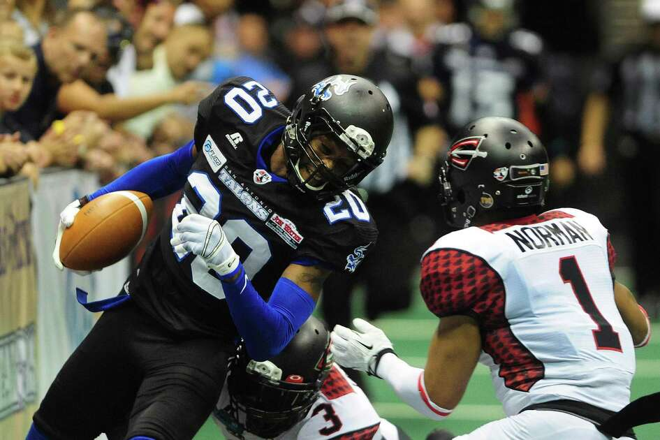 Receiver Clinton Solomon of the San Antonio Talons runs for yardage as LaRoche Jackson (3) and Marrio Norman of the Cleveland Gladiators defend during Arena Football League action in the Alamodome on Saturday, July 12, 2014.