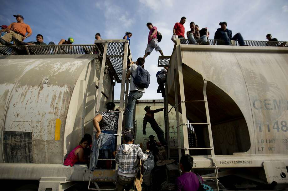 Central American migrants climb on a north bound train during their journey toward the U.S.-Mexico border, in Ixtepec, Mexico, Saturday, July 12, 2014. The number of unaccompanied minors detained on the U.S. border has more than tripled since 2011. Children are also widely believed to be crossing with their parents in rising numbers. (AP Photo/Eduardo Verdugo) Photo: Eduardo Verdugo, Associated Press