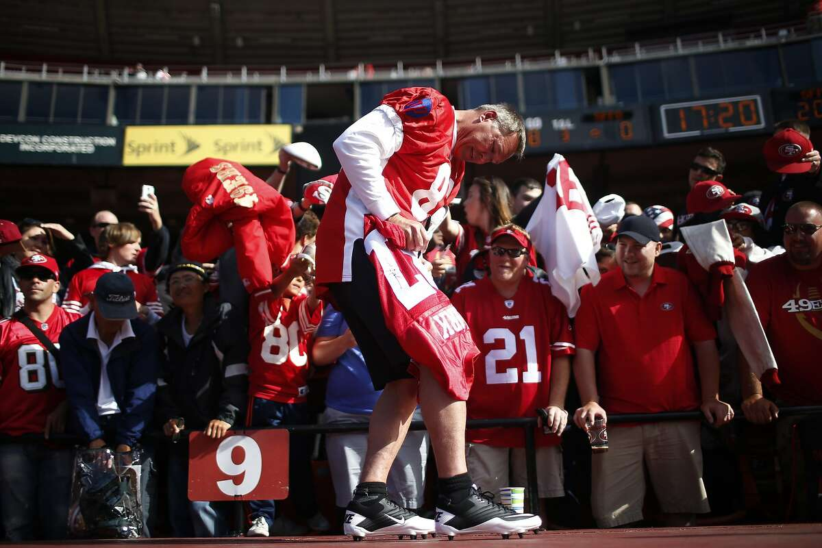 Former San Francisco 49ers wide receiver Dwight Clark, center, signs a autograph before the Legends of Candlestick flag football game at Candlestick Park in San Francisco, Calif. on Saturday, July 12, 2014.