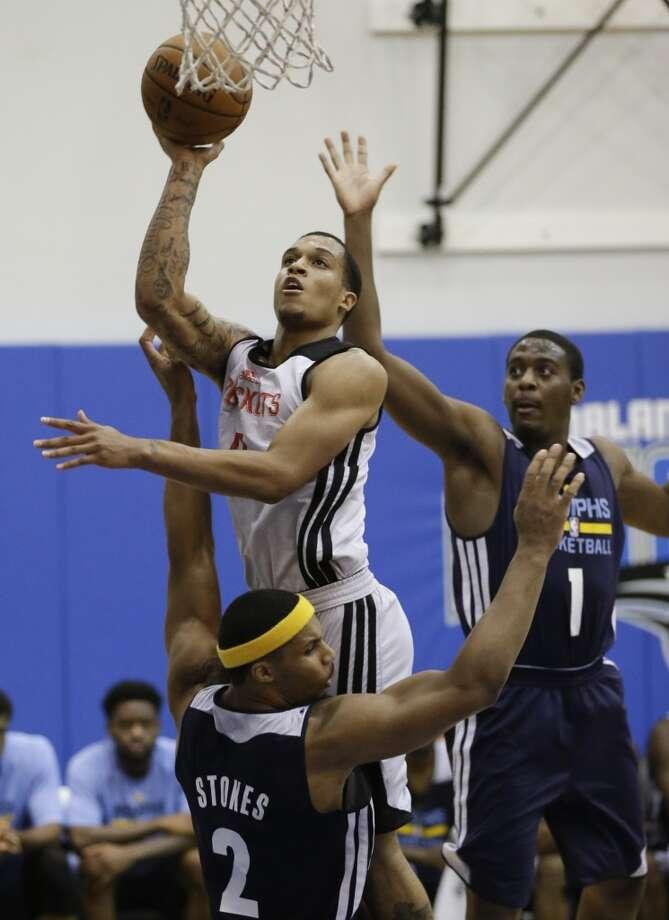 Jabari Brown, center, makes a shot between Jarnell Stokes (2) and Jordan Adams. Photo: John Raoux, Associated Press
