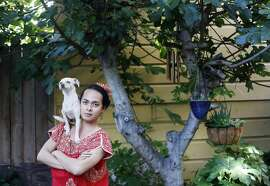With his dog Cali on his shoulder, artist Jean Franco Pilas honors Frida Kahlo in his San Francisco back yard.
