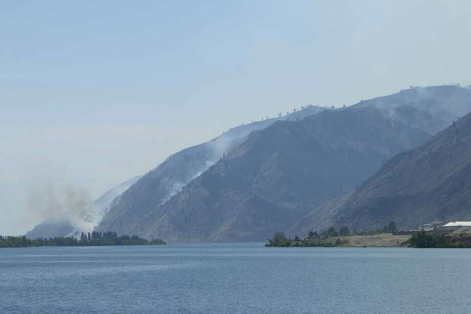 Smoke rises from the area of a wildfire near Entiat, Wash., Friday, July 11, 2014. Several hundred firefighters worked Friday to contain the fire that has burned grass and brush across nearly 30 square miles in central Washington. Photo: Rachel La Corte, AP  / AP