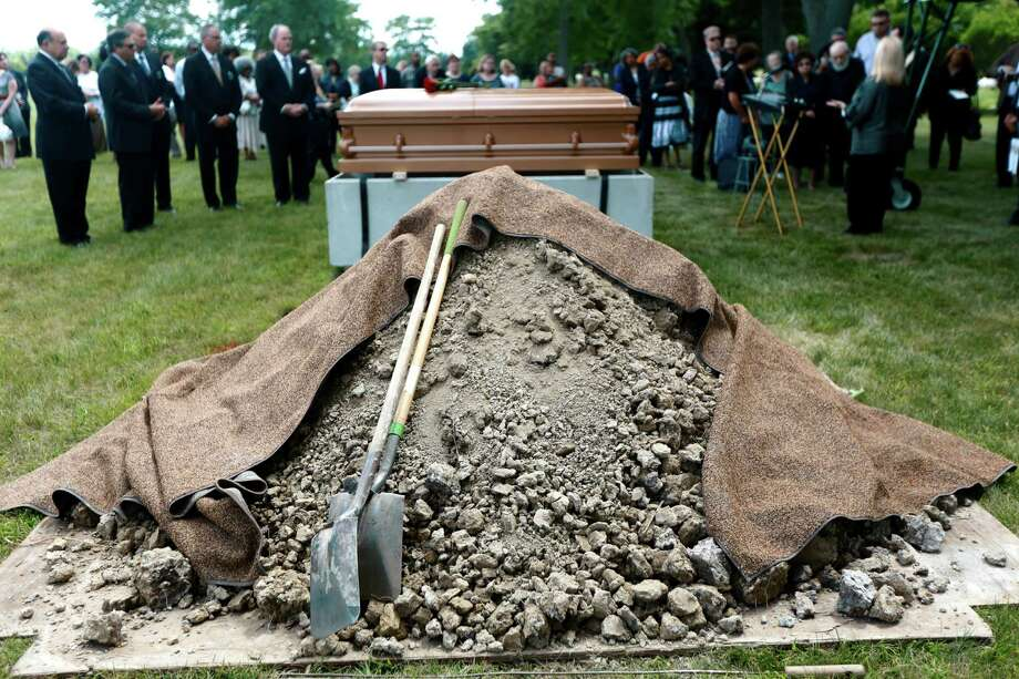 "Dirt is piled to the side for the burial of Richard Clement during the ""Service of Remembrance"" at Our Lady of Hope Cemetery in Brownstown Township, Mich., on Wednesday, July 9, 2014. With Wayne County unable to afford to bury 200 unclaimed bodies, the Jewish Fund, the Roman Catholic Archdiocese of Detroit and area funeral homes joined forces to ensure the bodies would get into individual graves. The coalition says all 200 bodies that have been sitting in the county morgue long-term will be laid to rest in individual, marked graves within 30 days. Most of the bodies go unclaimed when family members don�t have the means to pay for burial. (AP Photo/Detroit Free Press, Kimberly P. Mitchell)  DETROIT NEWS OUT;  NO SALES Photo: Kimberly P. Mitchell, AP  / Detroit Free Press"