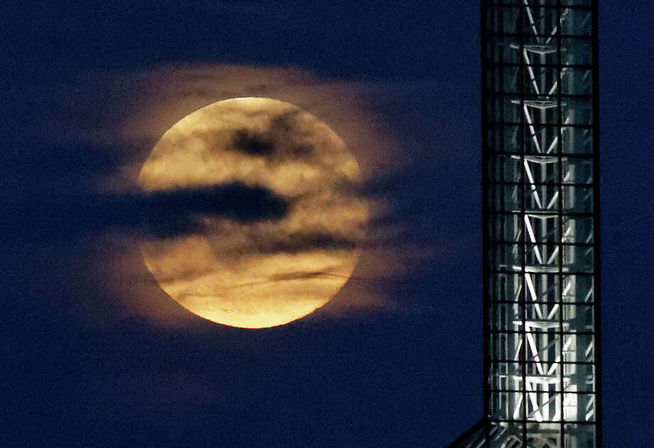 A supermoon rises over the Oregon Convention Center in Portland, Ore, Saturday, July 12, 2014. (AP Photo/The Oregonian, Mike Zacchino) MAGAZINES OUT; TV OUT; LOCAL TELEVISION OUT; LOCAL INTERNET OUT; THE MERCURY OUT; WILLAMETTE WEEK OUT; PAMPLIN MEDIA GROUP OUT Photo: Mike Zacchino, AP  / The Oregonian