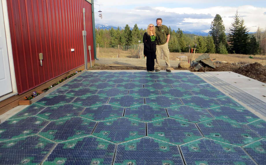 In this May 2014, photo provided by Solar Roadways, Scott and Julie Brusaw stand for a photo on a prototype solar-panel parking area at their company's business in Sandpoint, Idaho. Scott Brusaw's idea for solar-powered roads has gone viral and raised more than $1.4 million in crowdsourced funding. Brusaw is proposing to pave driveways, parking lots, bike trails and, eventually, highways with hexagon-shaped solar panels that will produce electricity and could even propel electric cars. Photo: Uncredited, AP  / AP2014