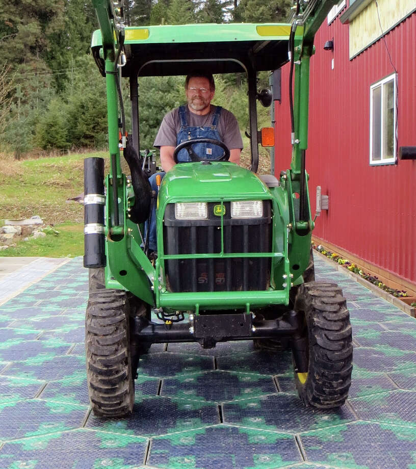 In this May 2014, photo provided by Solar Roadways, Scott Brusaw drives a tractor on a prototype solar-panel parking area at his company's business in Sandpoint, Idaho. Brusaw's idea for solar-powered roads has gone viral and raised more than $1.4 million in crowdsourced funding. Brusaw is proposing to pave driveways, parking lots, bike trails and, eventually, highways with hexagon-shaped solar panels that will produce electricity and could even propel electric cars. Photo: Uncredited, AP  / AP2014