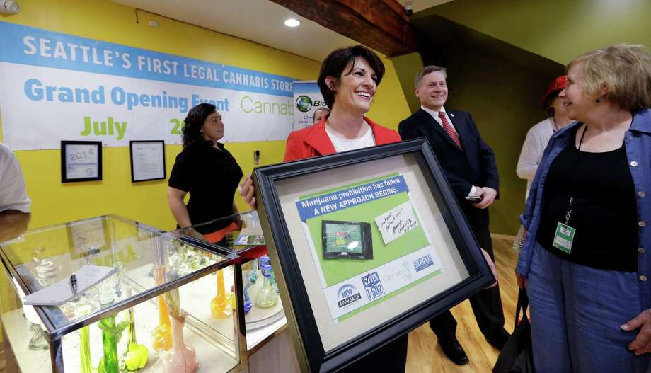 Alison Holcomb, left, criminal justice director at the Washington state ACLU, holds her framed first-purchase of legal marijuana as she stands with Seattle City Attorney Pete Holmes and state Sen. Jeanne Kohl- Welles at Cannabis City Tuesday, July 8, 2014, in Seattle, on the first day that sales of recreational pot became legal in the state. Washington on Tuesday became the second state to allow people to buy marijuana legally in the U.S. without a doctor's note as eager customers who lined up outside stores made their purchases and savored the moment. Photo: Elaine Thompson, AP  / Pool, AP