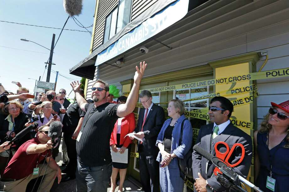Cannabis City owner James Lathrop addresses the crowd before a ceremonial ribbing cutting at his shop on the first day that sales of recreational pot became legal Tuesday, July 8, 2014, in Seattle.  Washington on Tuesday became the second state to allow people to buy marijuana legally in the U.S. without a doctor's note as eager customers who lined up outside stores made their purchases and savored the moment. Photo: Elaine Thompson, AP  / AP Pool