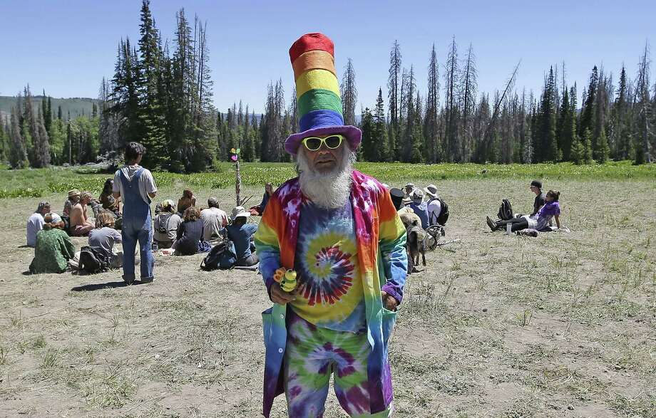 FILE - In this July 1, 2014, file photo, a man who identified himself as Glowing Feather walks along a trail in the Rainbow Family encampment, in the Uinta National Forest, Utah. Forest Service spokeswoman Kathy Jo Pollock says most of the nearly 8,000 people who were there at the height of the Rainbow Family festival have left. Pollock says there were 587 total incidents, including 31 arrests and 136 citations for violations. Two people died in their sleep during the event. The arrests included drug possession, drunken driving and public urination. Photo: Rick Bowmer, AP  / AP