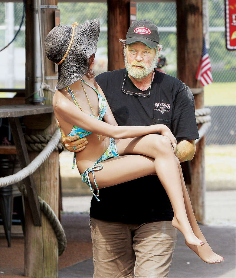 "Volunteer Dan Knoll carries one of the most important things to safety from the Hawg Pit BBQ Barn on West Main Street in Grafton, Ill., Monday July 7, 2014 as floodwaters neared the back of the business. Several female mannequins had to be ""rescued"" along with all of the other items in the bar Monday. Several more feet of floodwater are currently predicited before a crest on Saturday. Grafton sits at the confluence of the Illinois and Mississippi rivers. Photo: John Badman, AP  / The Telegraph"