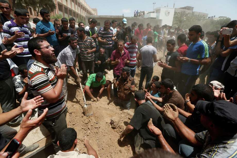 Palestinians offer their prayers over the grave of a member of the al-Batsh family who was killed in Saturday's Israeli airstrike, during a funeral procession in Gaza City on Sunday, July 13, 2014. The strike hit the home of Gaza police chief Taysir al-Batsh and damaged a nearby mosque as evening prayers ended Saturday, killing at least 18 people, wounding 50 and leaving some people believed to be trapped under the rubble, said Palestinian Health Ministry official Ashraf al-Kidra. Photo: Lefteris Pitarakis, AP  / AP2014