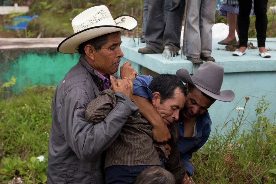 Two men grapple with Francisco Ramos, center, as he screams for his son, during the burial service of of his son Gilberto Francisco Ramos Juarez, a Guatemalan boy whose decomposed body was found in the Rio Grande Valley of South Texas, in San Jose Las Flores, Guatemala, Saturday, July 12, 2014. The 15-year-old Guatemalan migrant was buried in his hometown Saturday, nearly a month after he became a symbol of the perils facing unaccompanied children who have been flooding illegally into the U.S. Photo: Moises Castillo, AP  / AP