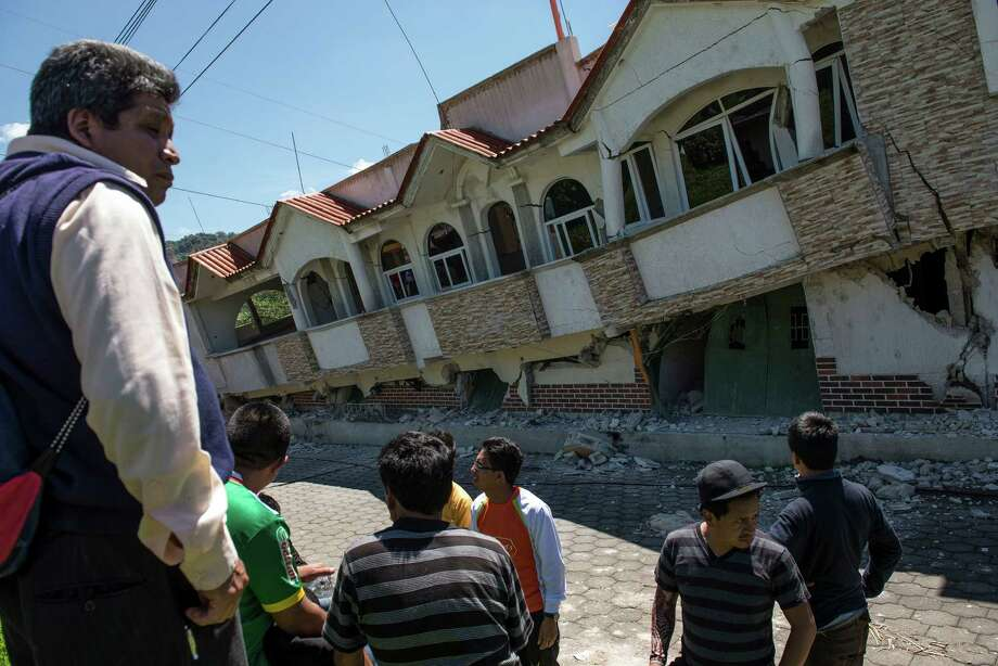 Neighbors gather outside homes that collapsed during an earthquake in San Pedro, Guatemala, Monday, July 7, 2014. A magnitude-6.9 earthquake on the Pacific Coast jolted a wide area of southern Mexico and Central America Monday. Photo: Oliver De Ros, AP  / AP2014
