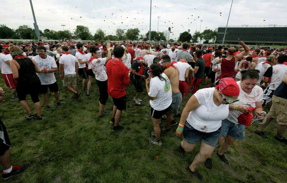 People participate in a tomato fight during The Great Bull Run on Saturday, July 12, 2014, in Cicero, Ill. It was the first time the event was held in the Chicago area. The run gives participants an opportunity to run with the bulls and attempts to mirror the San Fermin festival, in Pamplona, Spain. Photo: Stacy Thacker, AP  / AP