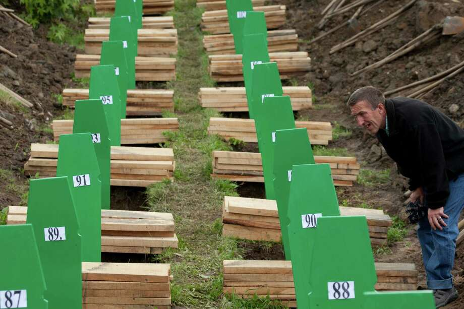 A Bosnian Muslim man searches for the grave of his relative in Srebrenica, Bosnia, Friday, July 11, 2014. Thousands of people gathered at the Potocari Memorial Center for a memorial ceremony and funeral of 175 victims of Europe's worst massacre since World War II. Photo: Amel Emric, AP  / AP