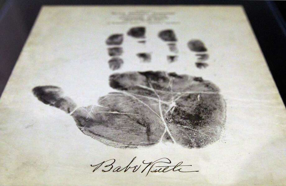 Babe Ruth's autograph is seen below a 1934 palm print, Wednesday, July 9, 2014, in Baltimore, during a media preview of sports memorabilia slated for auction to mark the 100th anniversary of his major league debut. The auction is scheduled to take place July 12, the day after the anniversary, and the organizers estimate that 125 items to be auctioned off could fetch as much as $10 million. Photo: Patrick Semansky, AP  / AP2014