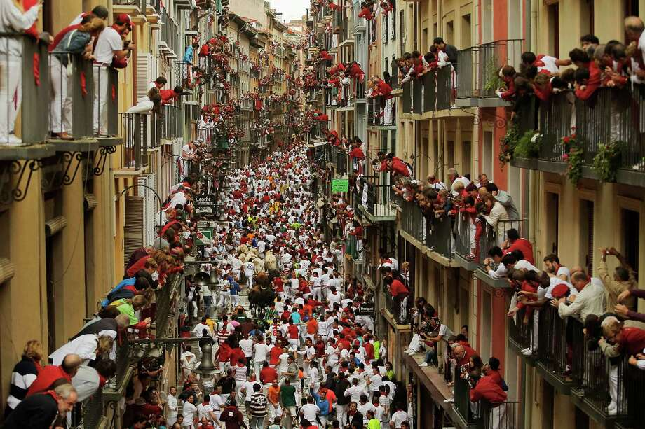 People watch as FuenteYmbro fighting bulls and revelers run during the running of the bulls, at the San Fermin festival, in Pamplona, Spain, Saturday July 12, 2014. Revelers from around the world arrive in Pamplona every year to take part in some of the eight days of the running of the bulls. Photo: Andres Kudacki, AP  / AP2014