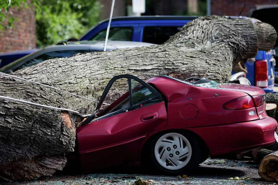 A downed tree lies atop a crushed car Wednesday, July 9, 2014, in Philadelphia. About 228,000 homes and businesses across Pennsylvania remain without power after severe thunderstorms raced across the state. Photo: Matt Rourke, AP  / AP2014
