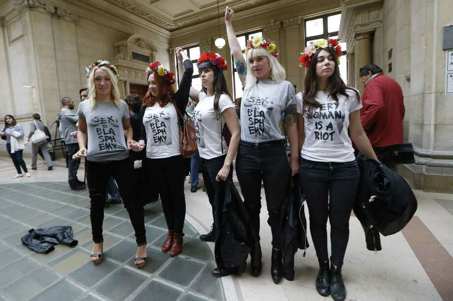 "Aactivists from the women's rights organisation Femen wave arms as they pose at a Paris courthouse after attending the trial of nine other Femen members, on July 9, 2014 in Paris. The nine women are accused of ""damage to a place of worship in a group"" after participating in a demonstration at Notre-Dame de Paris in February 2013. AFP PHOTO / THOMAS SAMSON        (Photo credit should read THOMAS SAMSON/AFP/Getty Images) Photo: THOMAS SAMSON, Getty Images  / AFP"