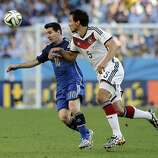 Argentina's Lionel Messi, left, battles for the ball with Germany's Mats Hummels during the World Cup final soccer match between Germany and Argentina at the Maracana Stadium in Rio de Janeiro, Brazil, Sunday, July 13, 2014. (AP Photo/Matthias Schrader)