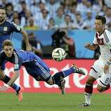 Argentina's Lucas Biglia, center, heads the ball clear from Germany's Mesut Ozil, right, during the World Cup final soccer match between Germany and Argentina at the Maracana Stadium in Rio de Janeiro, Brazil, Sunday, July 13, 2014. (AP Photo/Matthias Schrader)