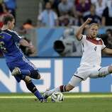 Argentina's Lucas Biglia fires a shot past Germany's Benedikt Hoewedes during the World Cup final soccer match between Germany and Argentina at the Maracana Stadium in Rio de Janeiro, Brazil, Sunday, July 13, 2014. (AP Photo/Victor R. Caivano)