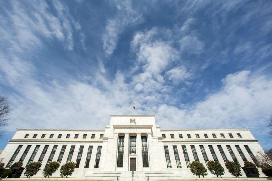 This file photo shows the Federal Reserve headquarters building in Washington. The super wealthy will benefit most from ending the Fed's low-interest rate policies. Photo: J. David Ake, Associated Press / AP
