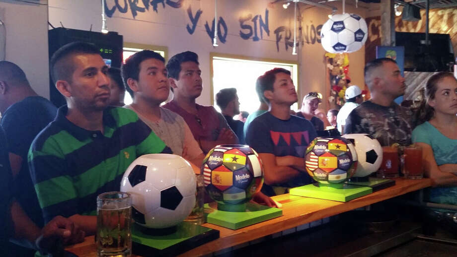 Fans watch the World Cup at Ojos Loco on the Northwest Side of town. A manger said about 375 people are watching the game in the standing room only sports bar. Photo: By J. Almendarez, By J. Almendarez, Express-News