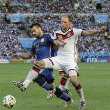 Argentina's Ezequiel Lavezzi, left, is challenged by Germany's Benedikt Hoewedes during the World Cup final soccer match between Germany and Argentina at the Maracana Stadium in Rio de Janeiro, Brazil, Sunday, July 13, 2014. (AP Photo/Victor R. Caivano)