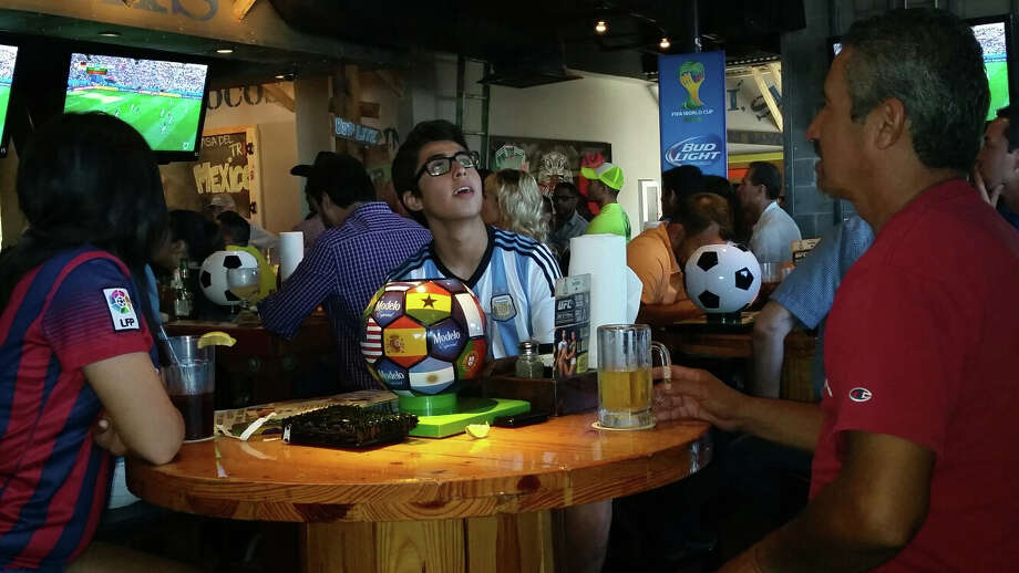 Julian Torres watches the World Cup at Ojos Locos sports bar on the Northwest Side of town. He and his family are all rooting for Argentina to win the Championship against Germany. The score is tied 27 minutes in to the game. Photo: J. Almendarez, By J. Almendarez, Express-News