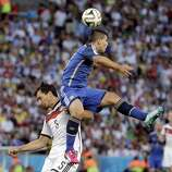 Argentina's Sergio Aguero goes up to head the ball over Germany's Mats Hummels during the World Cup final soccer match between Germany and Argentina at the Maracana Stadium in Rio de Janeiro, Brazil, Sunday, July 13, 2014.
