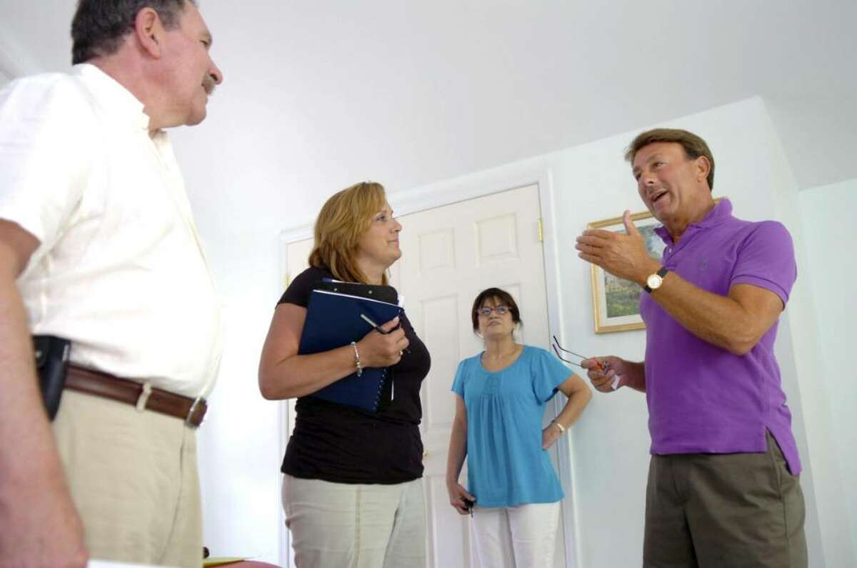 """Real estate agent Maxwell Wiesen, pictured at right showing a condominium last year to Carol Fischer, with Doug Clark, from Zip Realty, and Fischer's friend Marie Bayer, was extremely busy in December and January, but this month has been dead. He calls the market """"shockingly overpriced."""""""