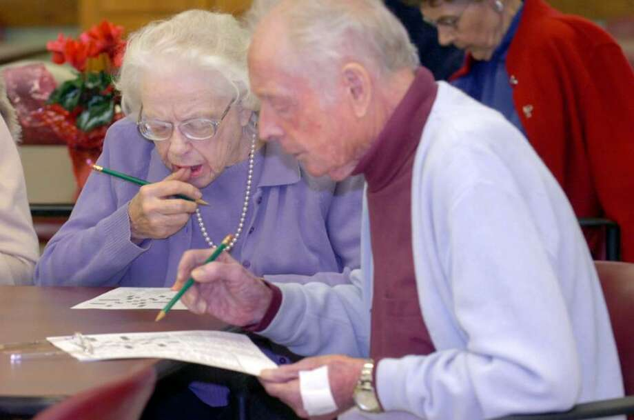 Evelyn Lucashu and her friend Joe Muskus puzzling over the crossword puzzle in the class by Ed Stein on solving crossword puzzles at the Greenwich Senior Center, on Wednesday, February 17, 2010. Photo: Helen Neafsey / Greenwich Time